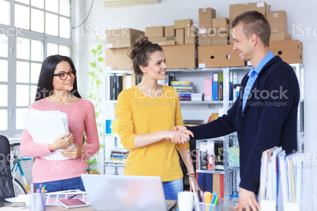 Young people in handshake at the office stock photo