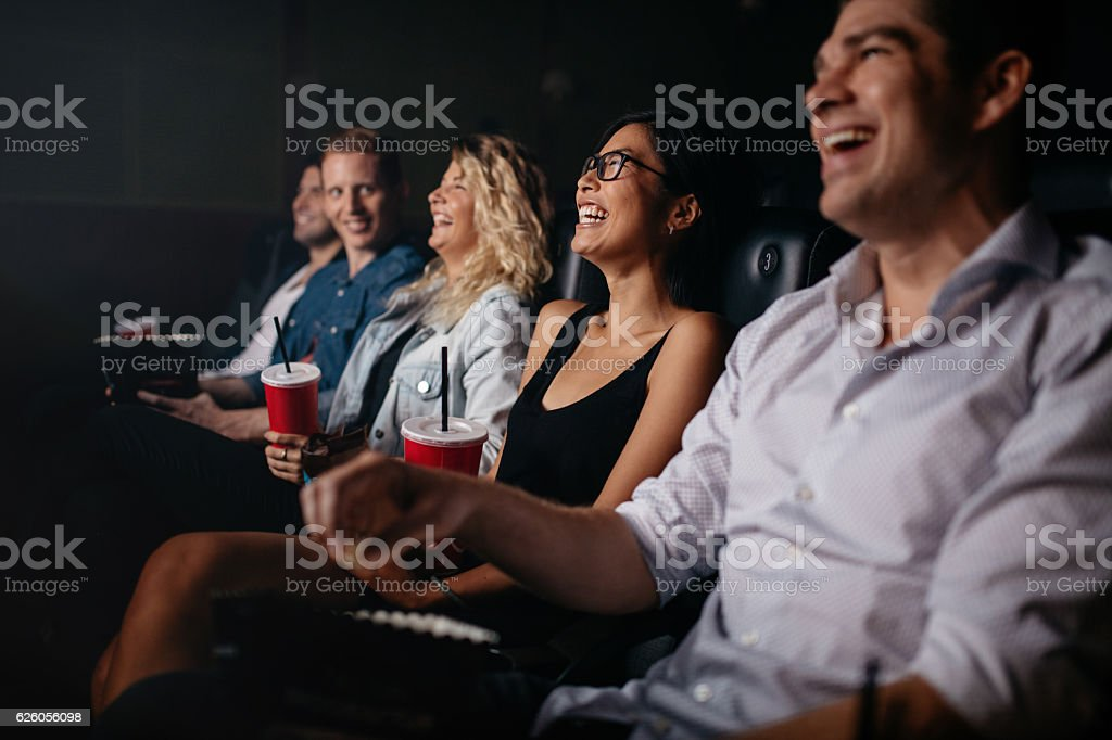 Young people in theater watching movie and smiling stock photo