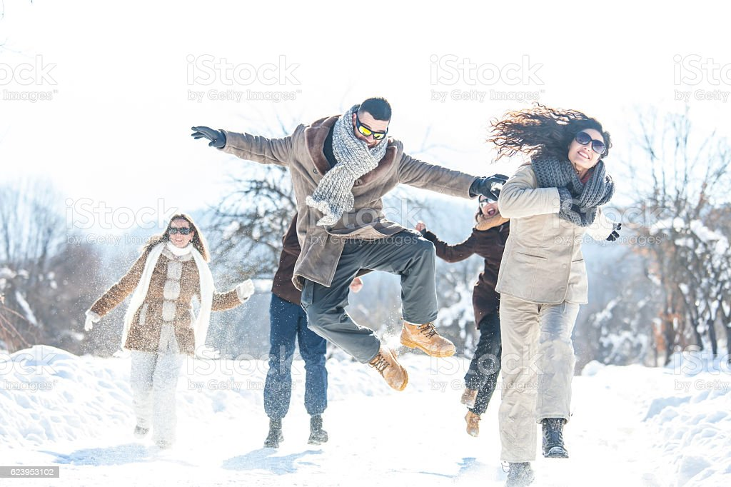 Young people jumping and having fun in the snow stock photo