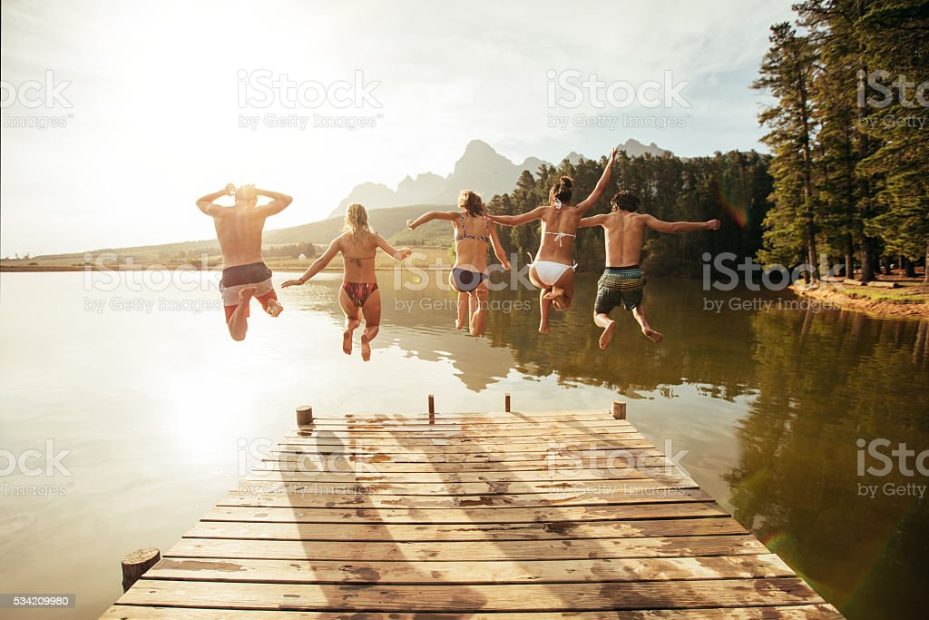 Young people jumping from pier into lake together stock photo