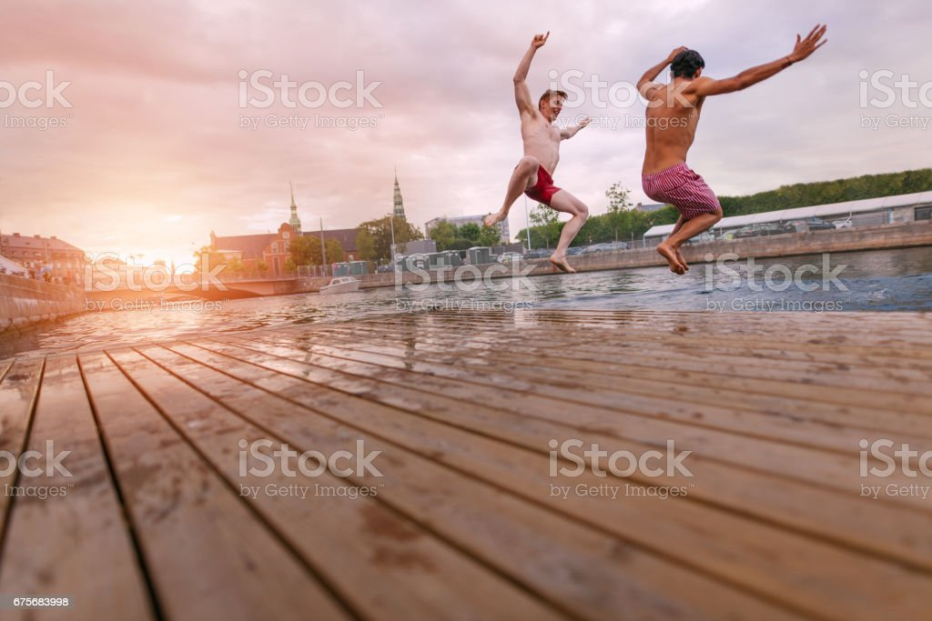 Young people jumping into lake in city stock photo