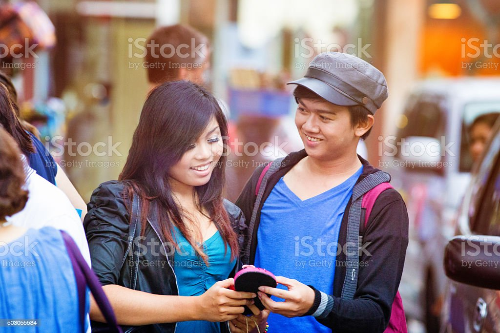 Young people looking at sandal in Indonesian street market stock photo