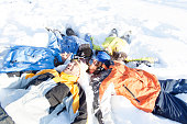 Young people lying down on snow and making snow angels