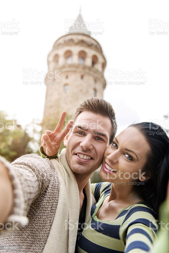 Young people making a selfie in front of Galata Tower stock photo