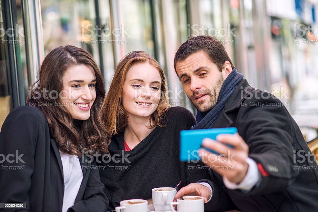 Young people making selfie in parisien cafe stock photo