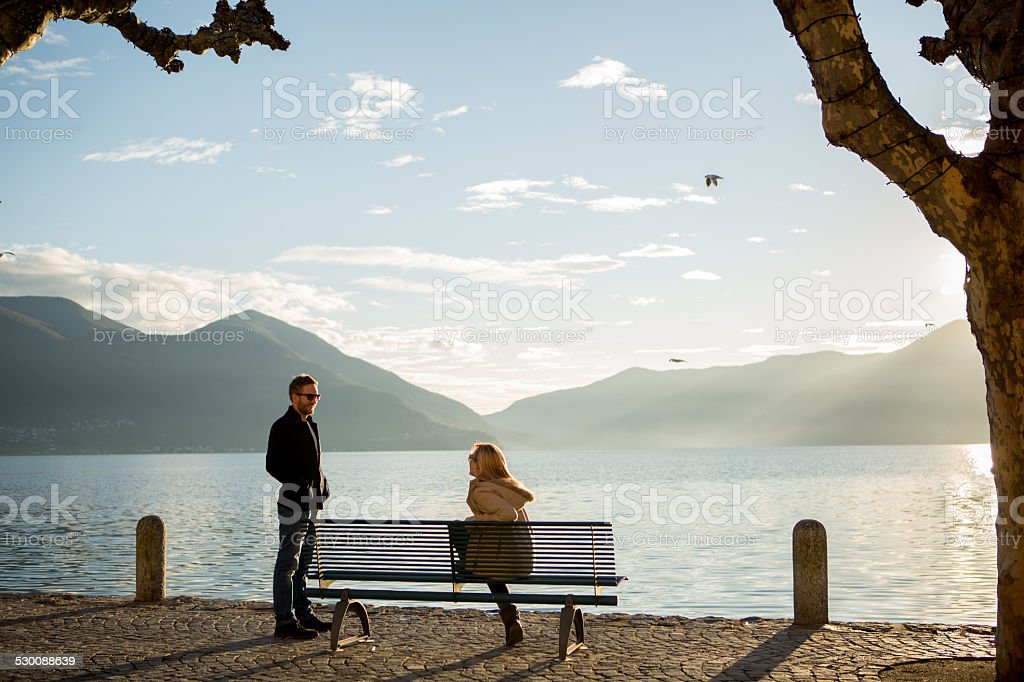 Young people on bench near lake chatting stock photo