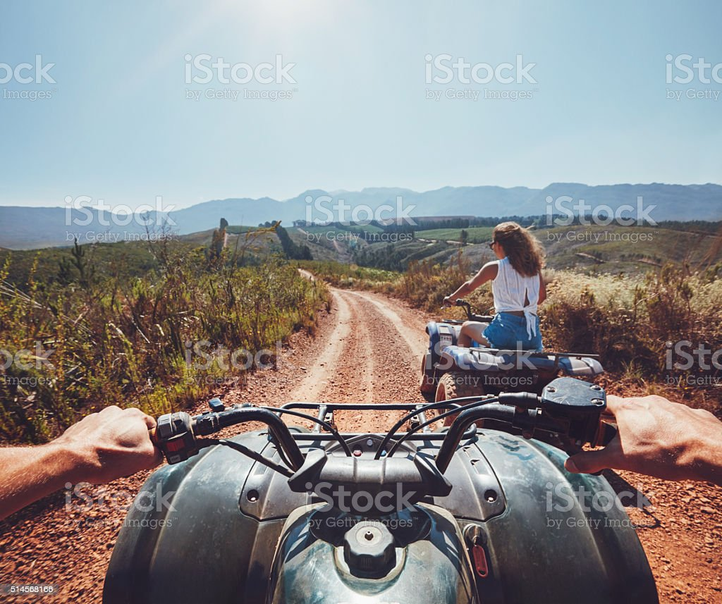 Young people on quad bikes on mountain trail stock photo