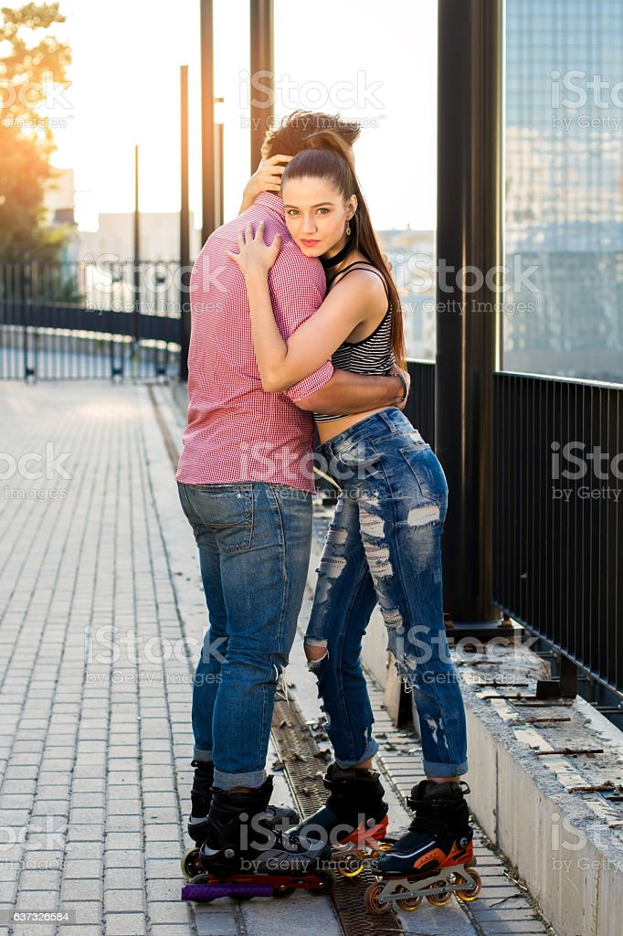 Young people on rollerblades hugging. stock photo