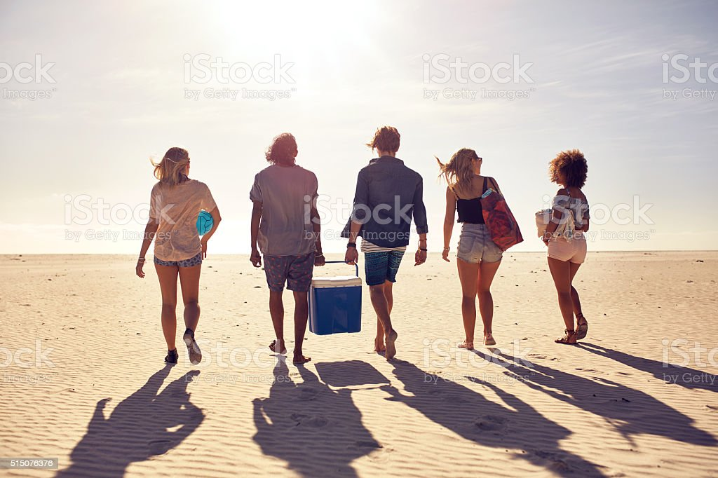 Young people on the beach carrying a cooler box stock photo
