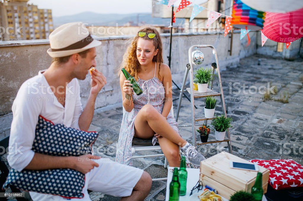 Young people partying on terrace with drinks at sunset stock photo
