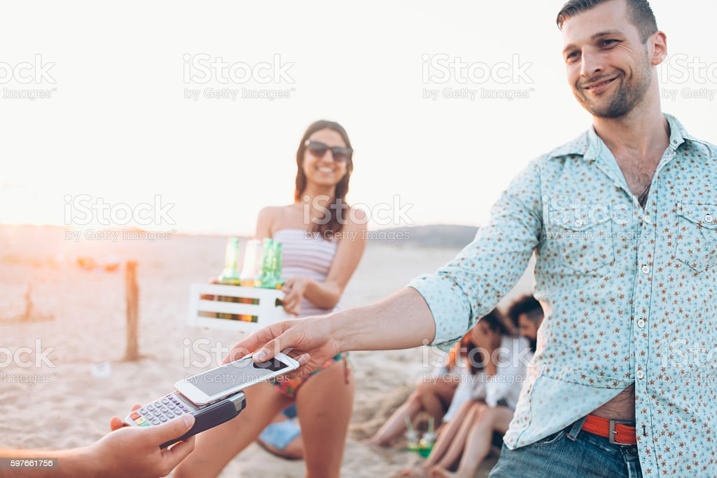 Young people paying with smart phone on beach stock photo