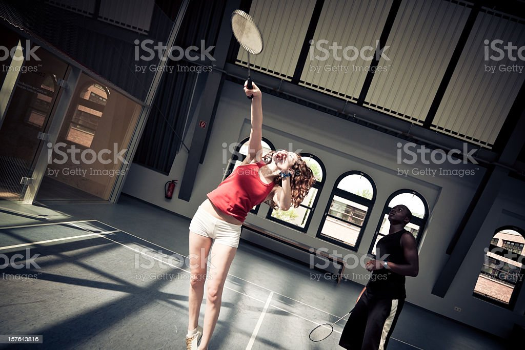 young people playing badminton at the gym stock photo