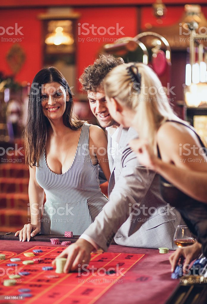 Young people playing roulette at the casino stock photo
