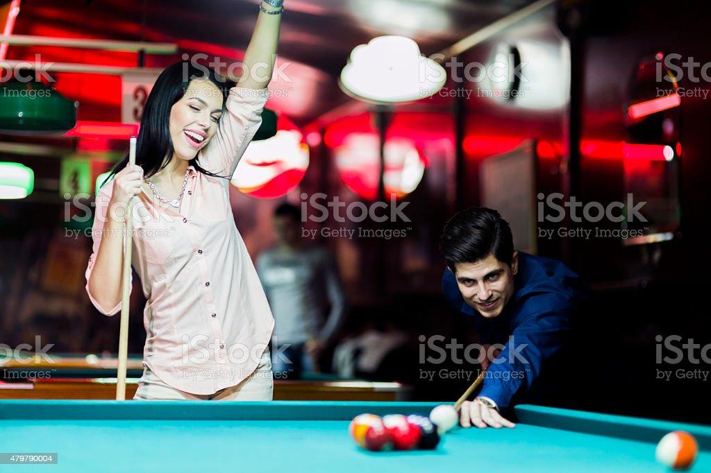 Young people playing billiard in a club pub bar