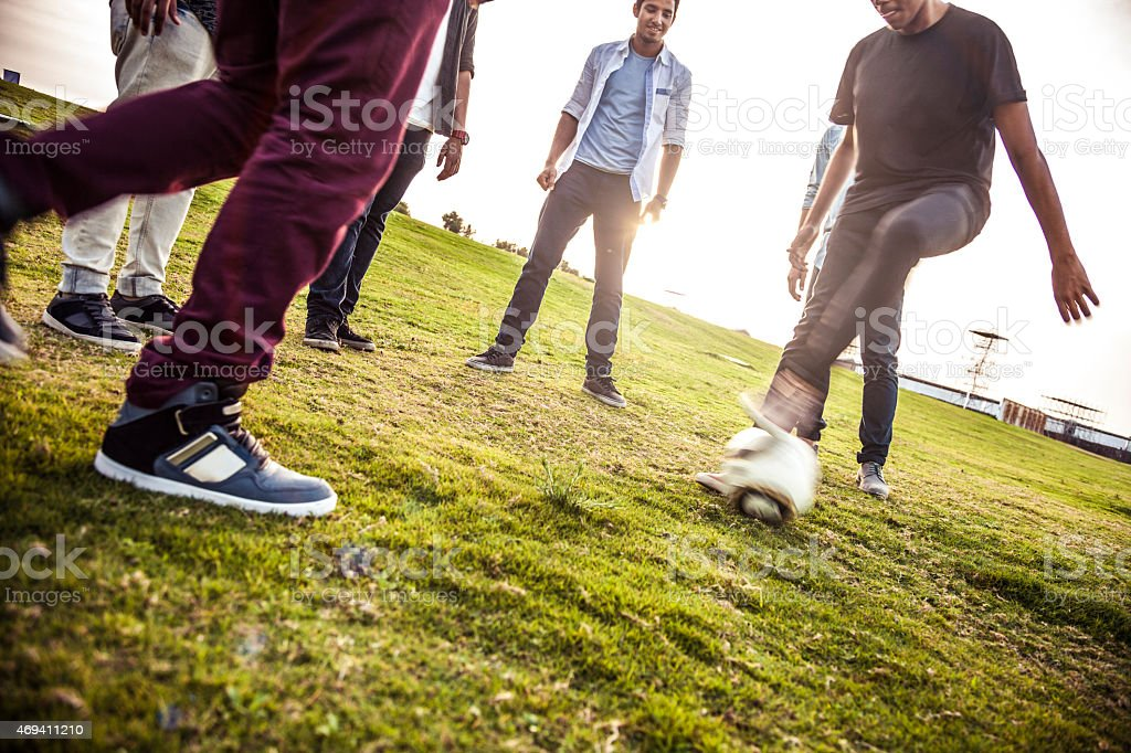 Young people playing soccer in a park stock photo