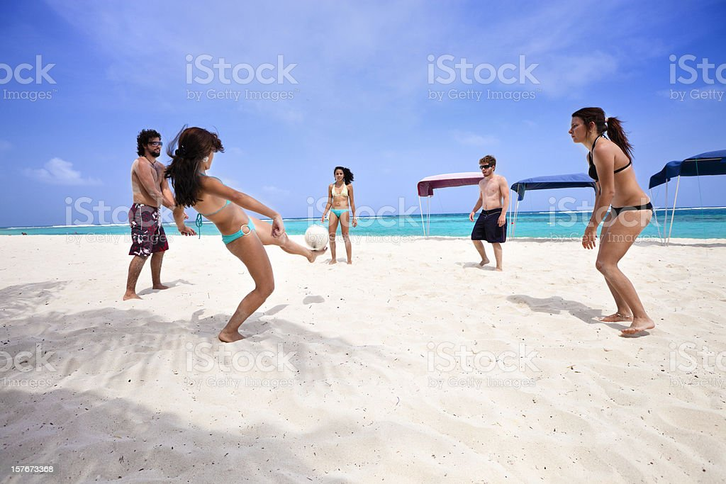 Young people playing soccer on a Tropical beach royalty-free stock photo