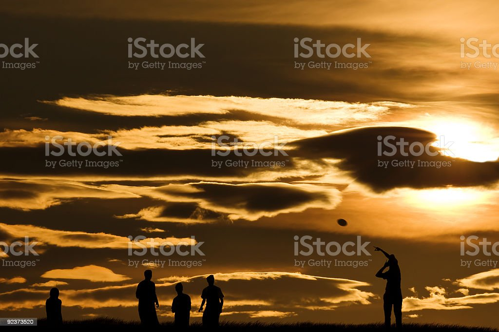 Young people playing with a ball in the sunset. stock photo
