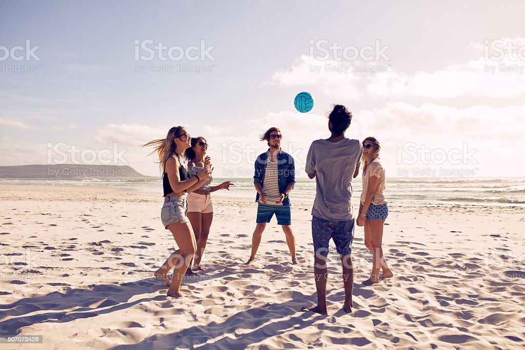 Young people playing with ball at the beach stock photo