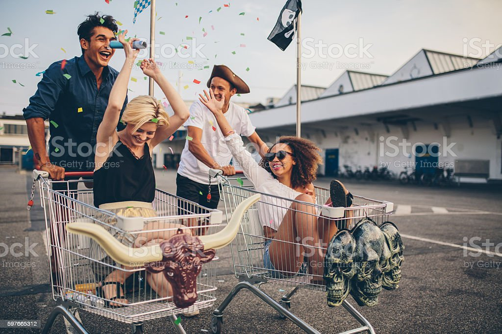 Young people racing with shopping cart and celebrating with confetti stock photo