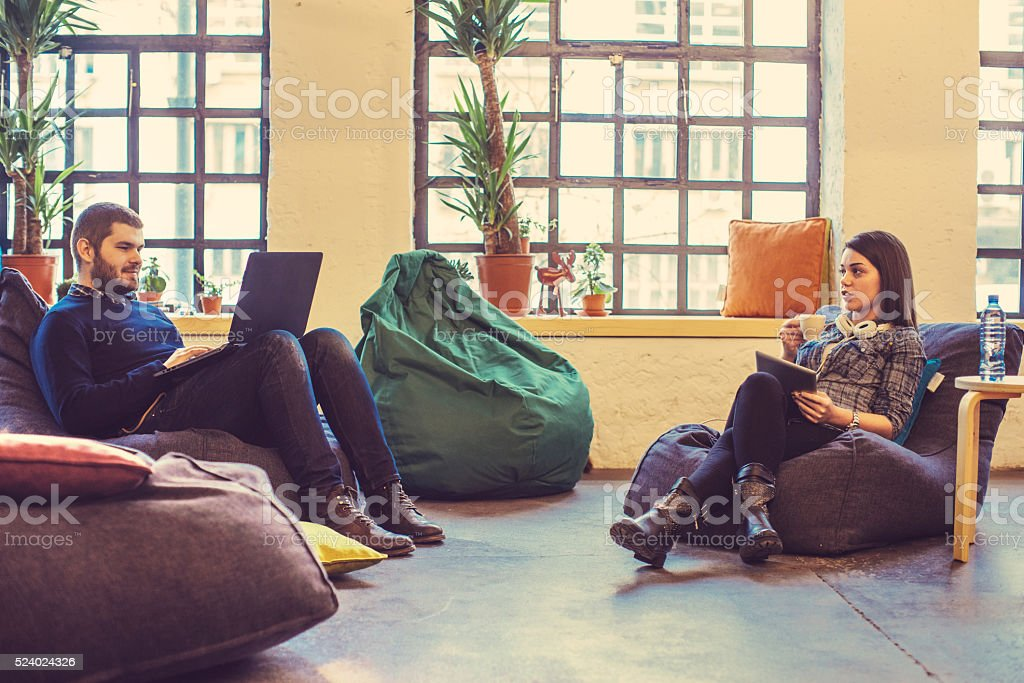 young people relaxing at the office stock photo