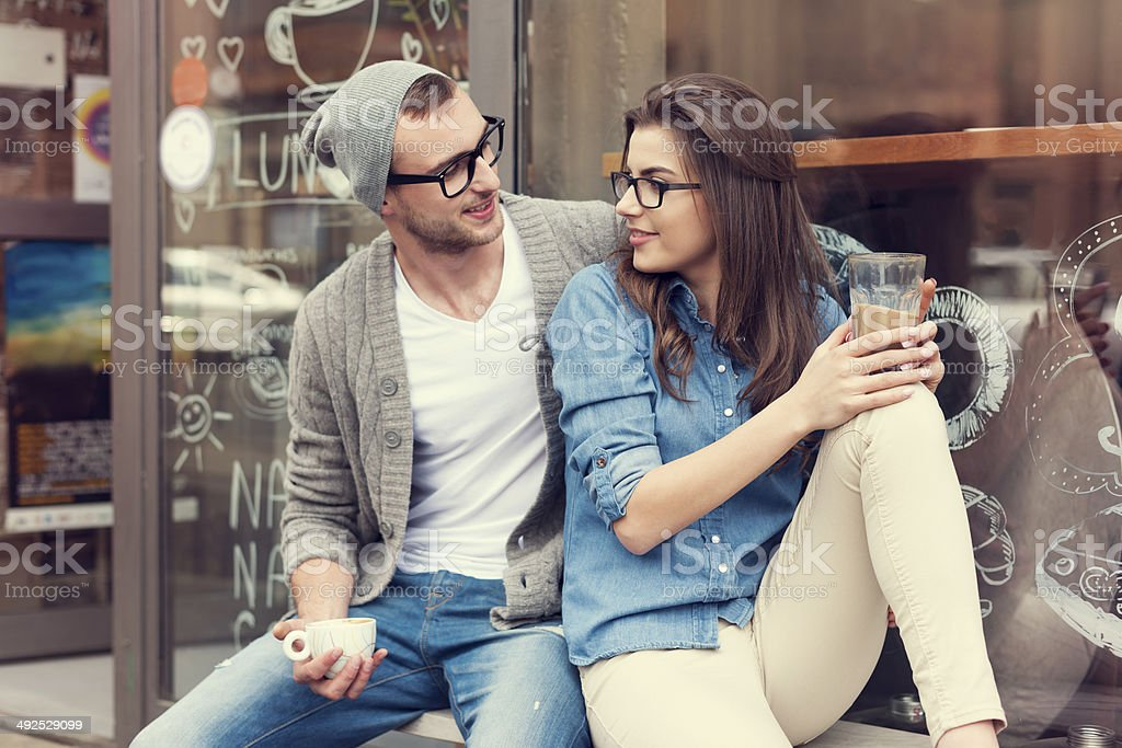 Young people relaxing with cup of coffee outside the cafe stock photo