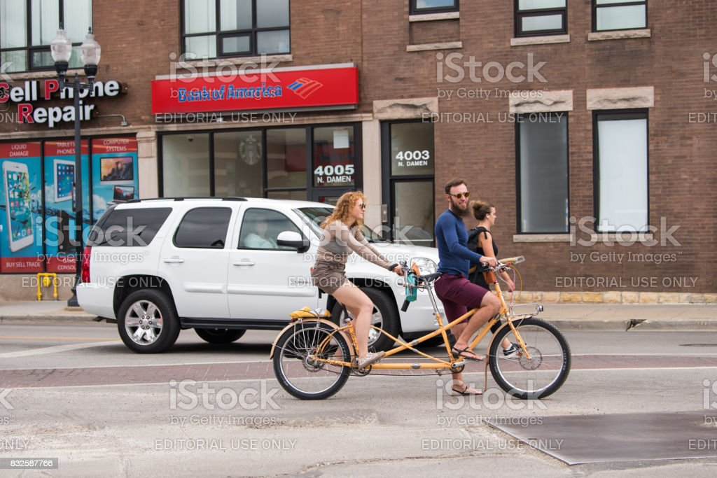 Young people ride a tandem bike in North Center, Chicago stock photo