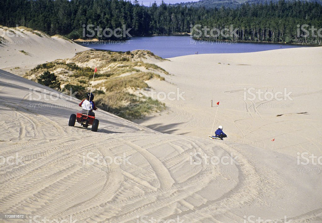 Young people riding in ATVs on sand dunes royalty-free stock photo