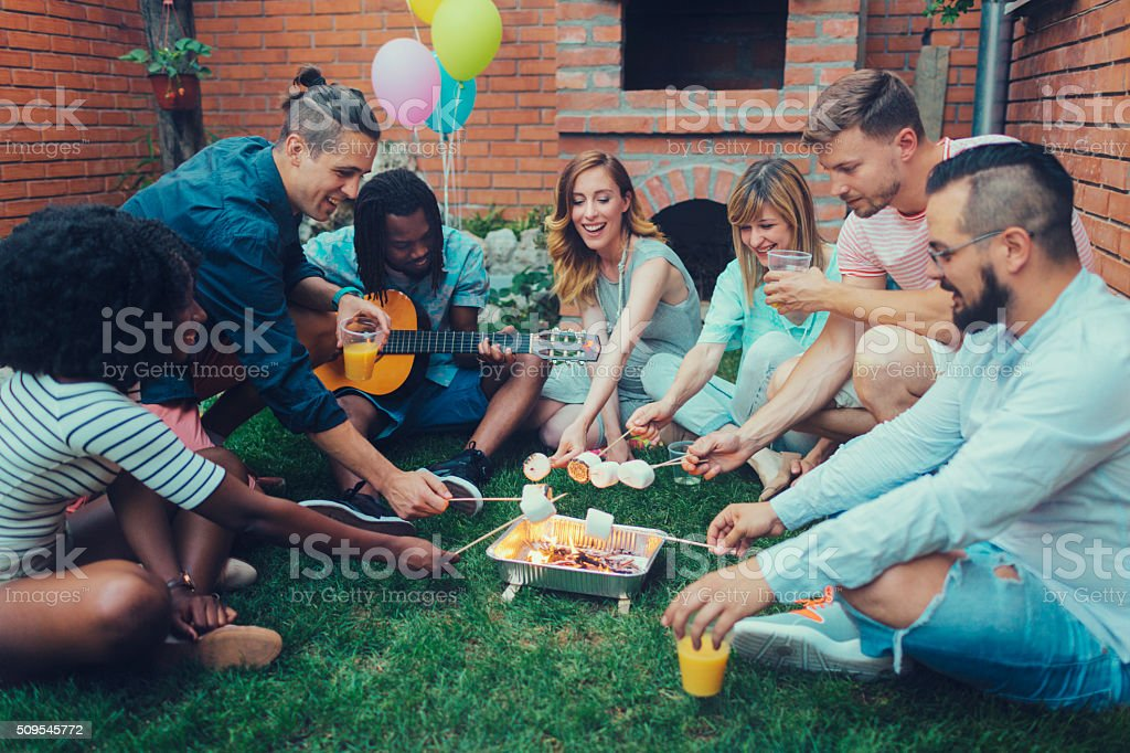 Young People Roasting Marshamllows On Open Fire stock photo