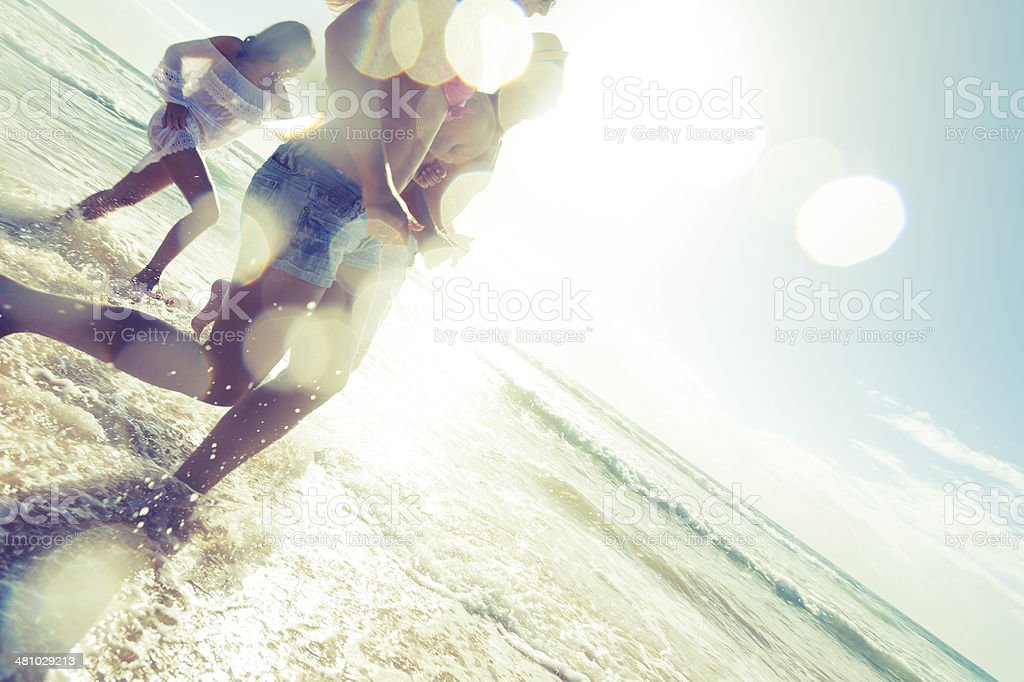 Young people running on the beach stock photo