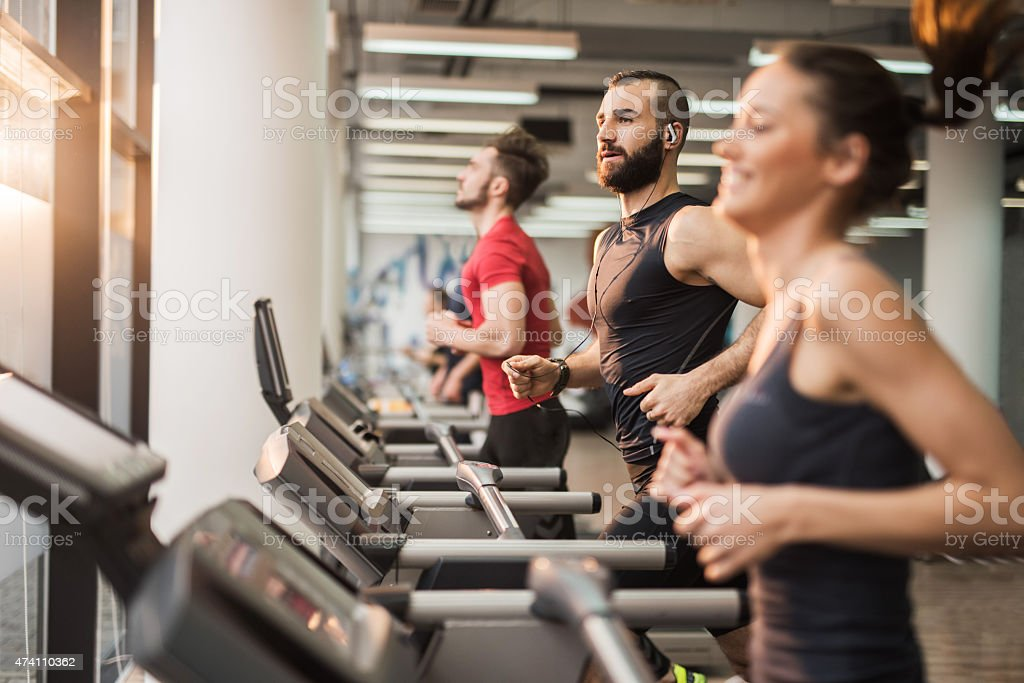 Young people running on treadmills in health club. stock photo