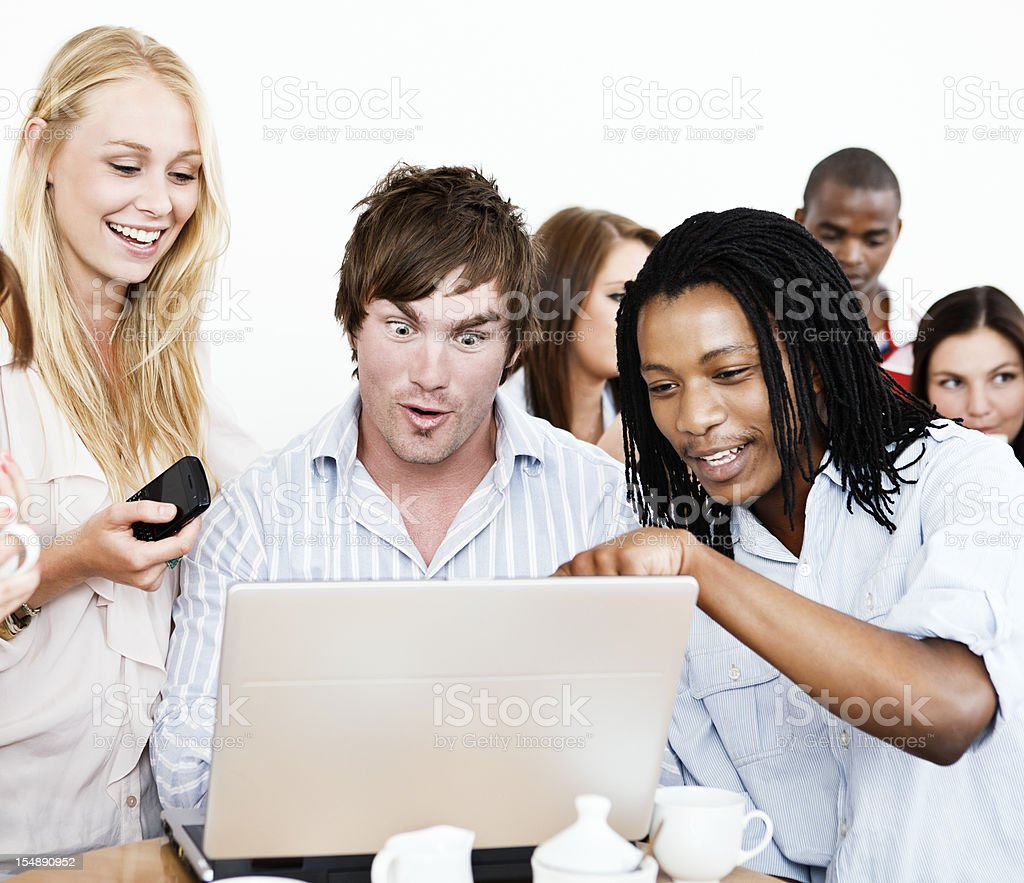 Young people shocked and amused by image on laptop royalty-free stock photo