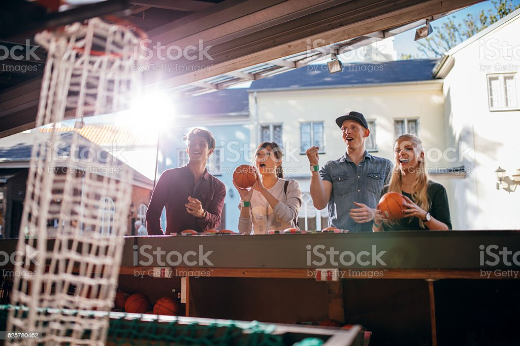 Young people shooting hoops at amusement park stock photo