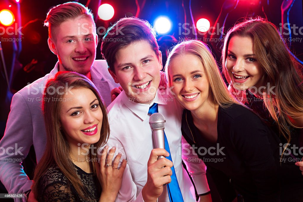 Young people singing at party stock photo