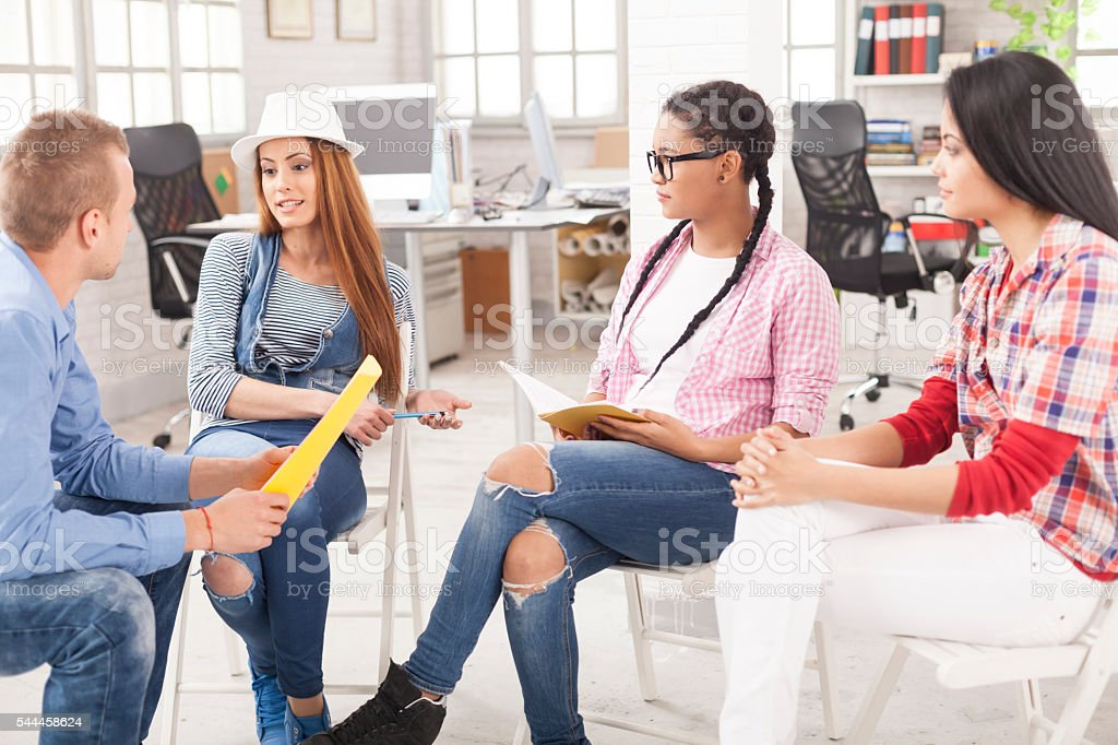 Young people sitting and discussing new ideas at workplace stock photo