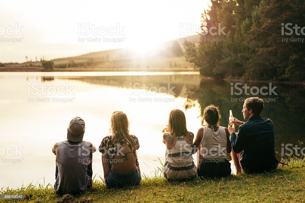 Young people sitting in a row by a lake stock photo