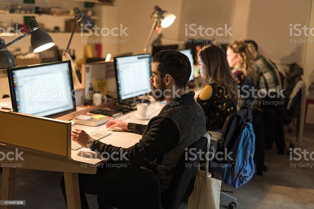Young people sitting in the office and working on computers. stock photo