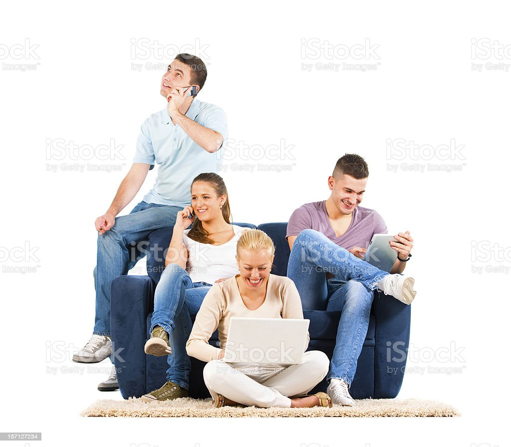 Young people sitting on the sofa with their gadgets royalty-free stock photo