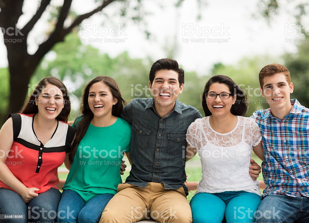 Young people sitting side by side and embracing stock photo