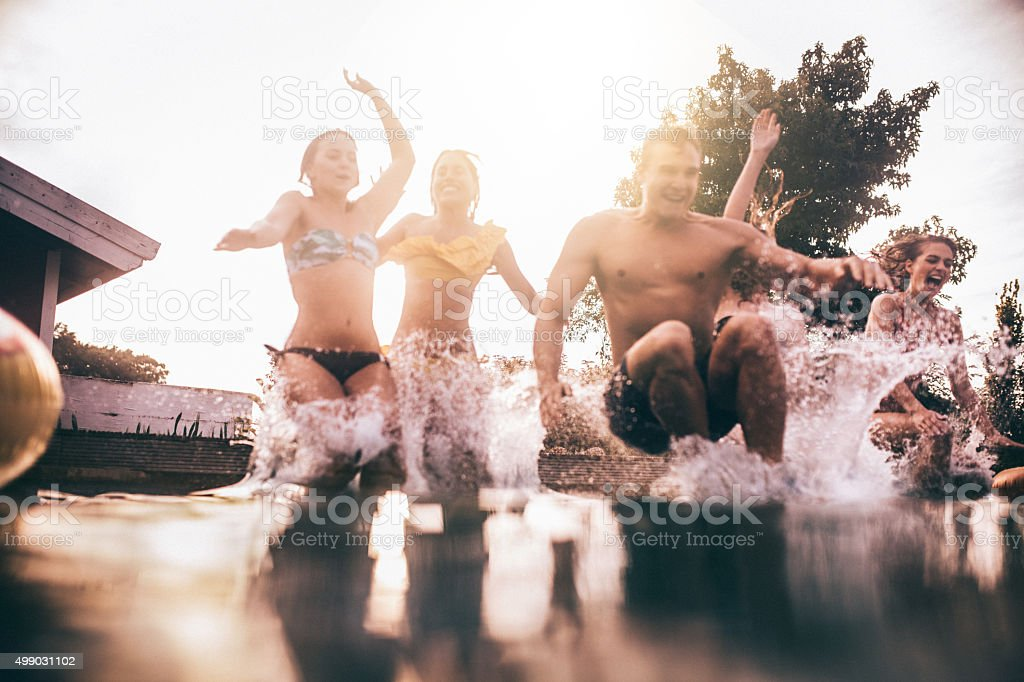 Young people splashing into a pool having jumped in together stock photo