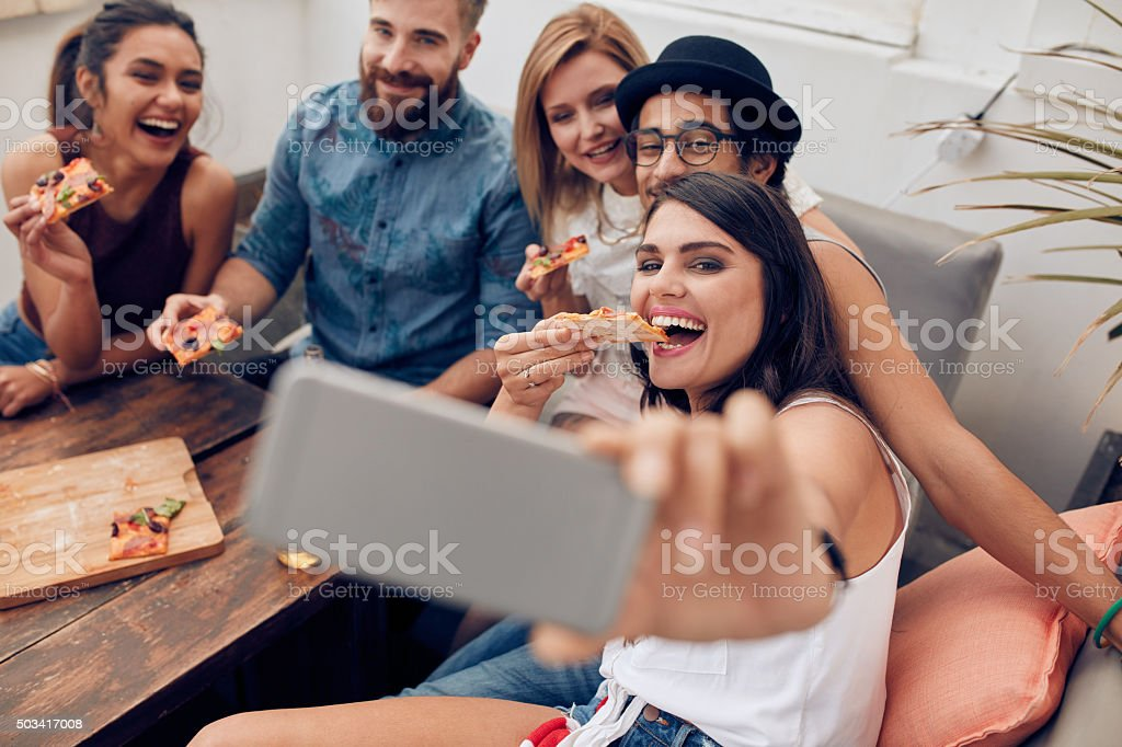 Group of multiracial young people taking a selfie while eating pizza....