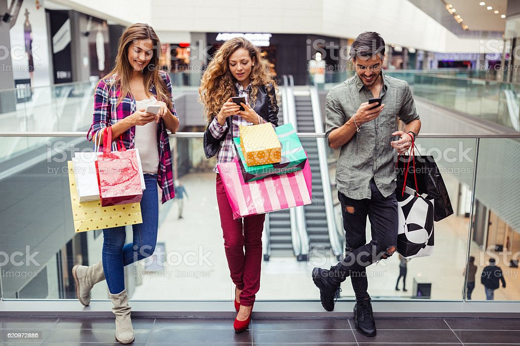 Young people texting in the shopping center stock photo