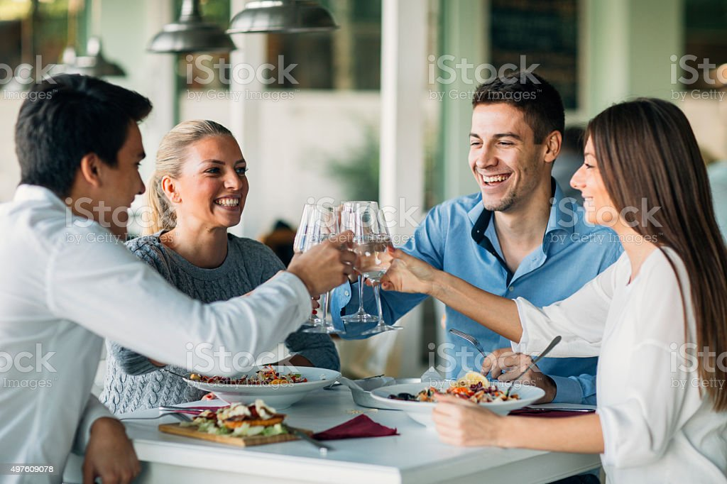 Young People Toasting In Restaurant. stock photo