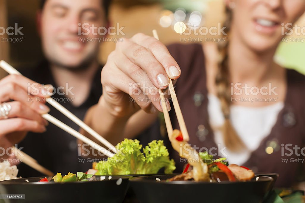 Young people using chop sticks on food in a Thai restaurant stock photo