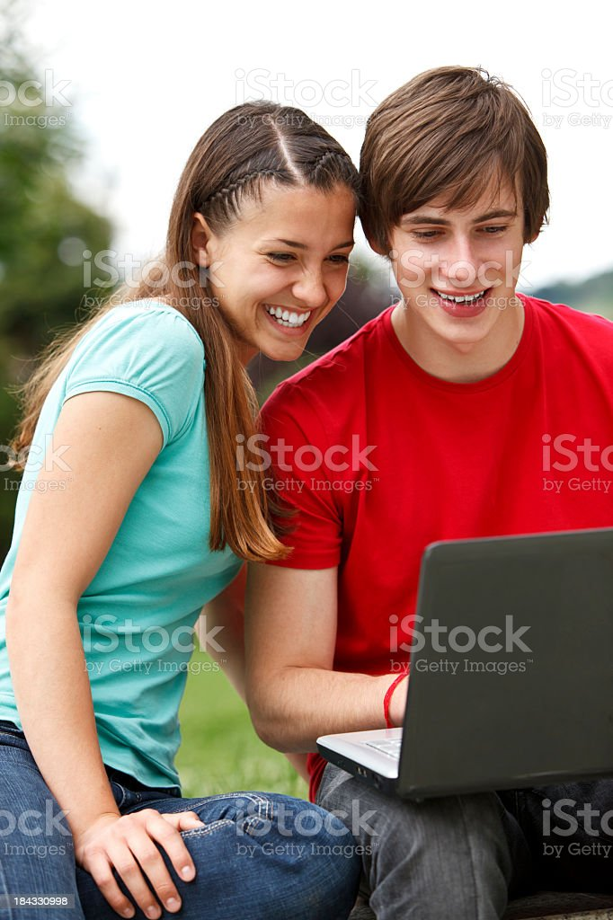 Young people using laptop outdoors royalty-free stock photo