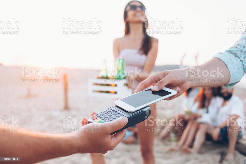 Young people using smart phone for paying on beach stock photo