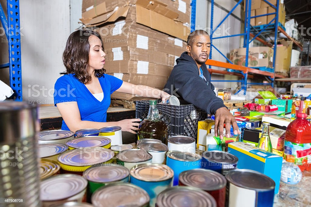 Young people volunteering to sort donations for charity food drive stock photo