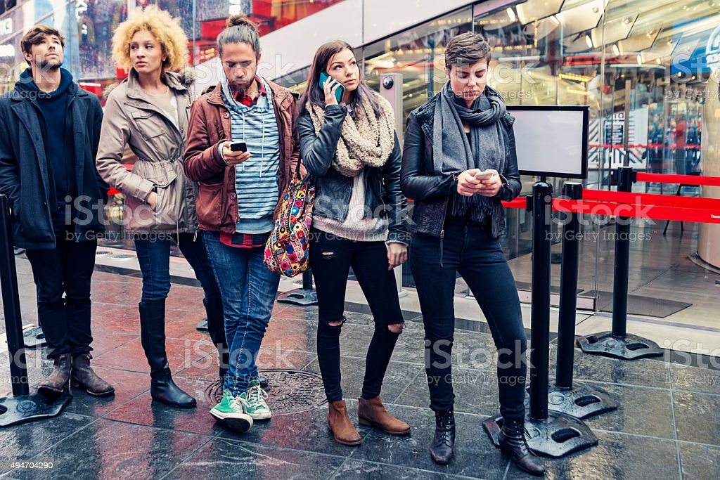 Young people waiting in line to buy tickets in NewYork. stock photo
