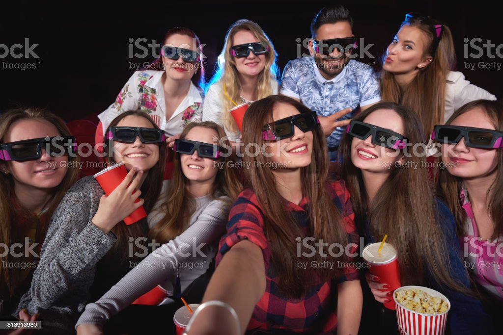 Young people watching 3D film at the movie theatre stock photo