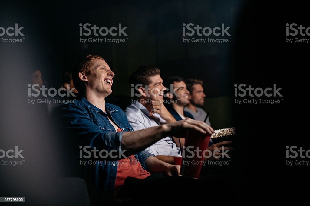 Young people watching comedy movie in theater stock photo