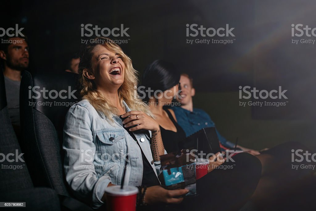 Young people watching movie and laughing stock photo